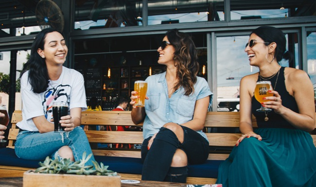 three ladies at restaurant have drinks outside