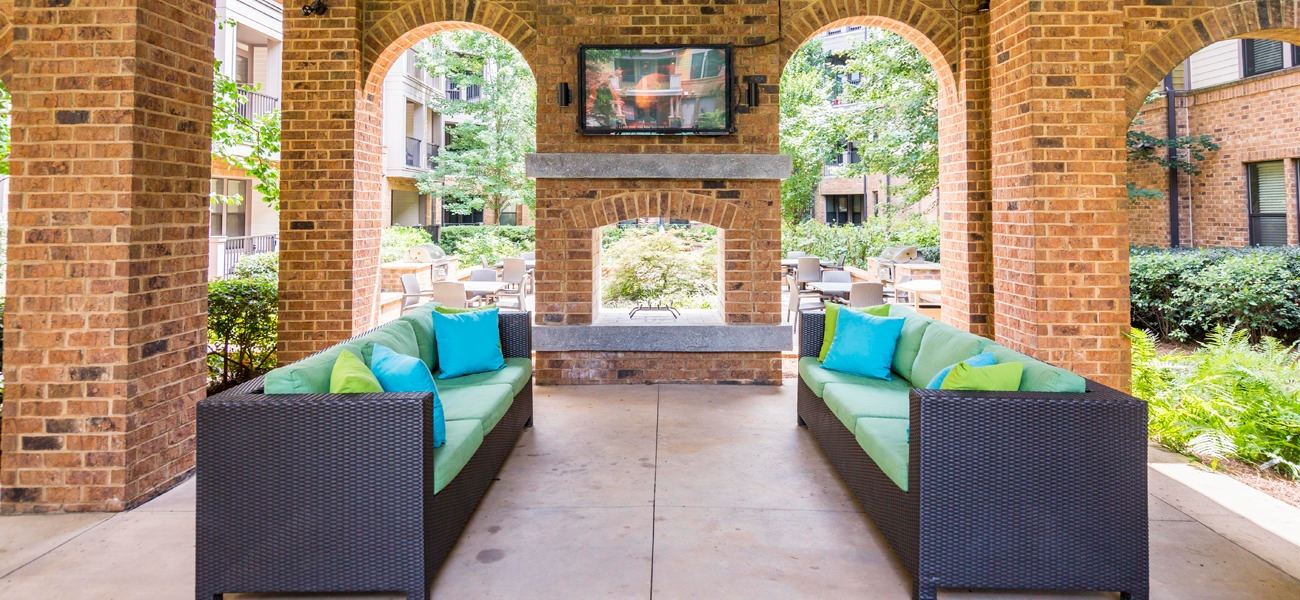 Outside patio area with couch seating and a TV.