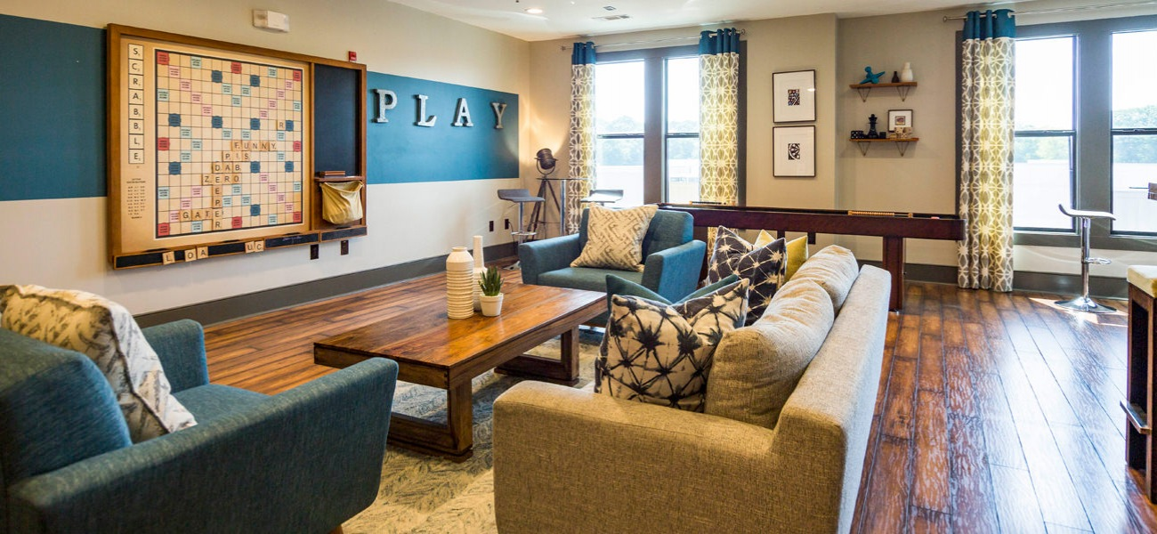 Clubhouse with couch, plush chairs, wall scrabble board and shuffle board table.